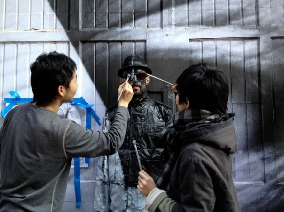 French street artist JR is being painted by Bolin's assistants in order to exactly match the background.